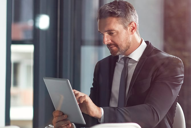 Man in suit using a tablet to track investments online