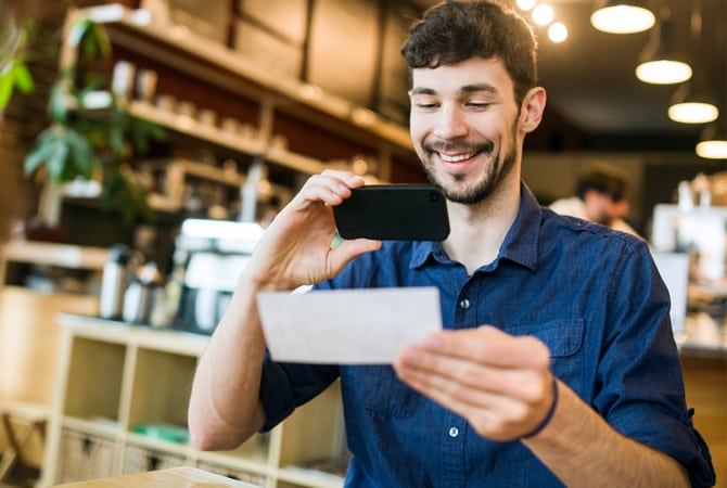 Man using his mobile phone to deposit a check in a coffee shop