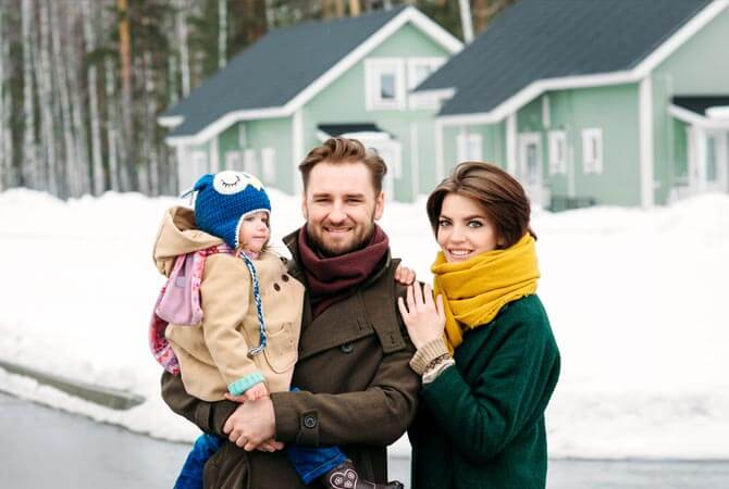 Family outside their home in winter