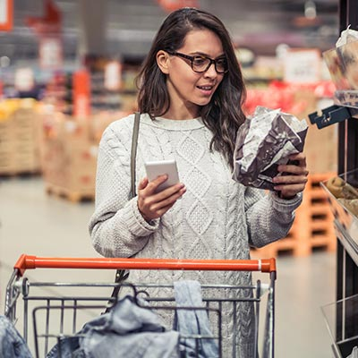 Woman using her shopping list on her phone at the grocery store