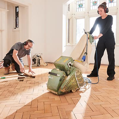 Husband and wife redoing hardwood floors with rented equipment