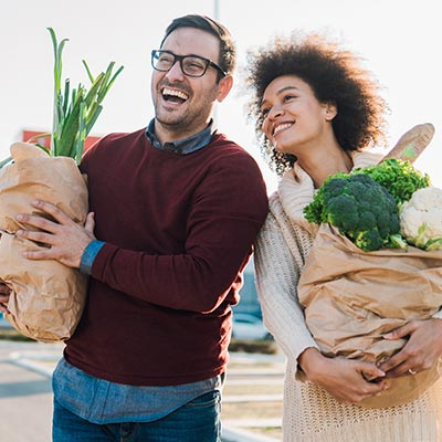 Couple walking with paper grocery bags filled with veggies