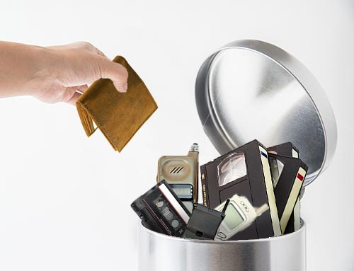 Wallet and old technology in trashcan