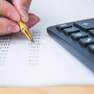 calculating taxes with calculator, pen, and paper